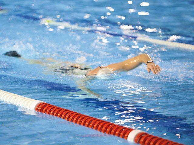 Frau schwimmt im Sportbecken des Bad Innenbereichs