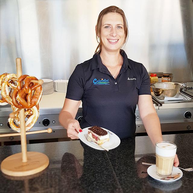 Junge Dame bietet Milchkaffee, Kuchen und Brezeln in der Gastronomie an