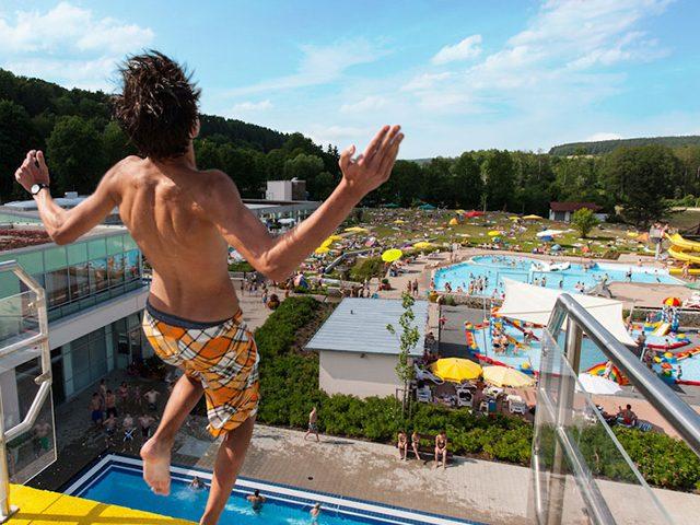 Mann auf Sprungturm mit Blick auf das Freibad