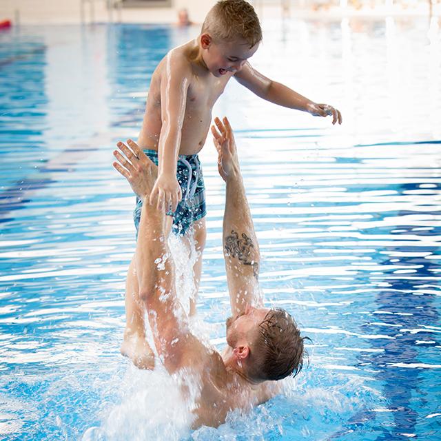 Mann wirft Jungen im Wasser in die Luft