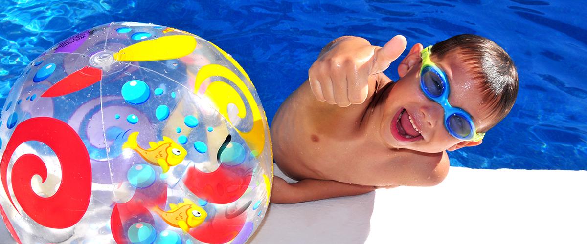Junge mit Taucherbrille und Wasserball mit Daumen nach oben