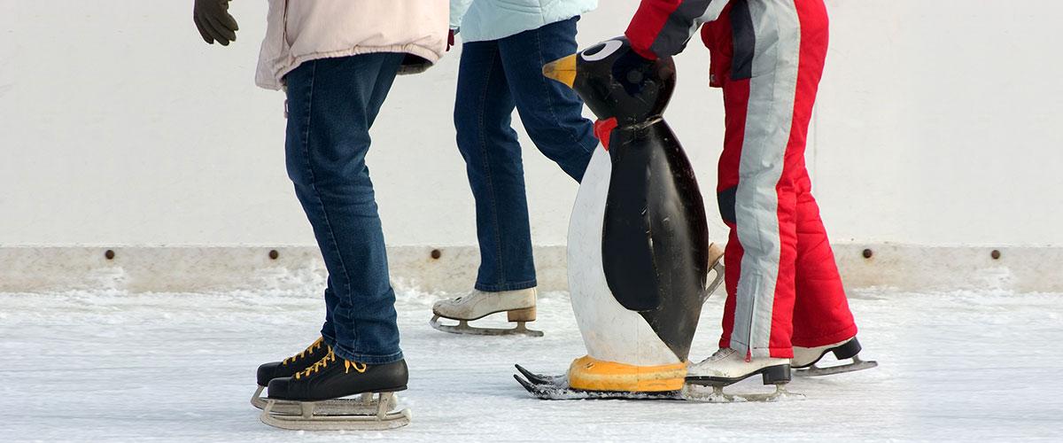 drei Personen mit Laufhilfe auf der Eislaufbahn